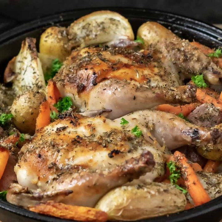 a cast iron skillet filled with Oven Roasted Cornish Hens and Veggies