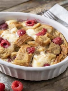 Raspberry Cream Cheese French Toast Casserole in a dish on a tray with a fork and napkin