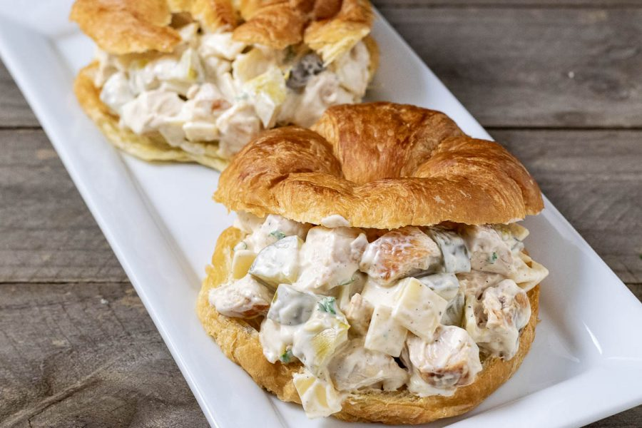 two chicken salad croissant sandwiches on a platter