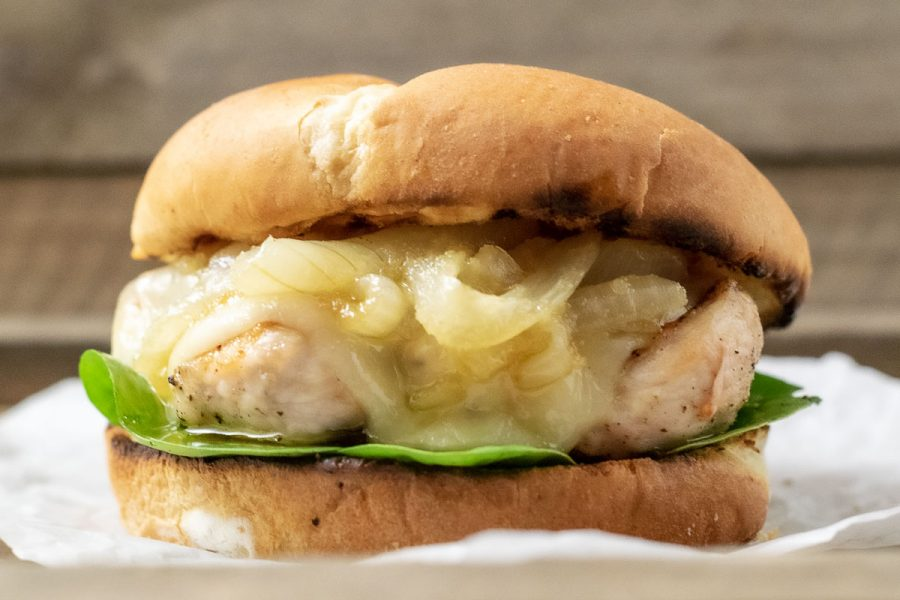 a close up front view of a french onion chicken sandwich on a crumpled paper