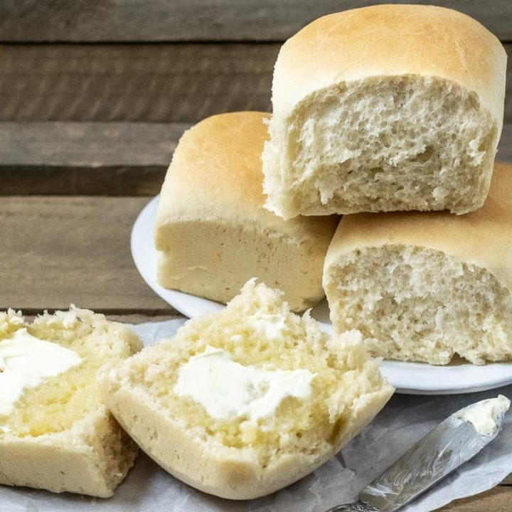 three dinner rolls stacked on a plate and one dinner roll cut open is spread with butter