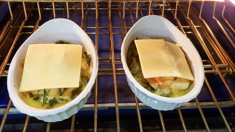 white cheddar slices added to top of baked stuffed chicken in two dishes inside oven