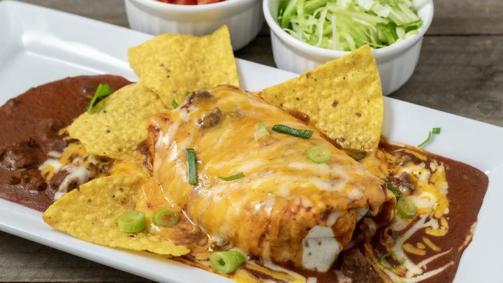 a large wet burrito on a platter with tortilla chips and sides of diced tomato and shredded lettuce