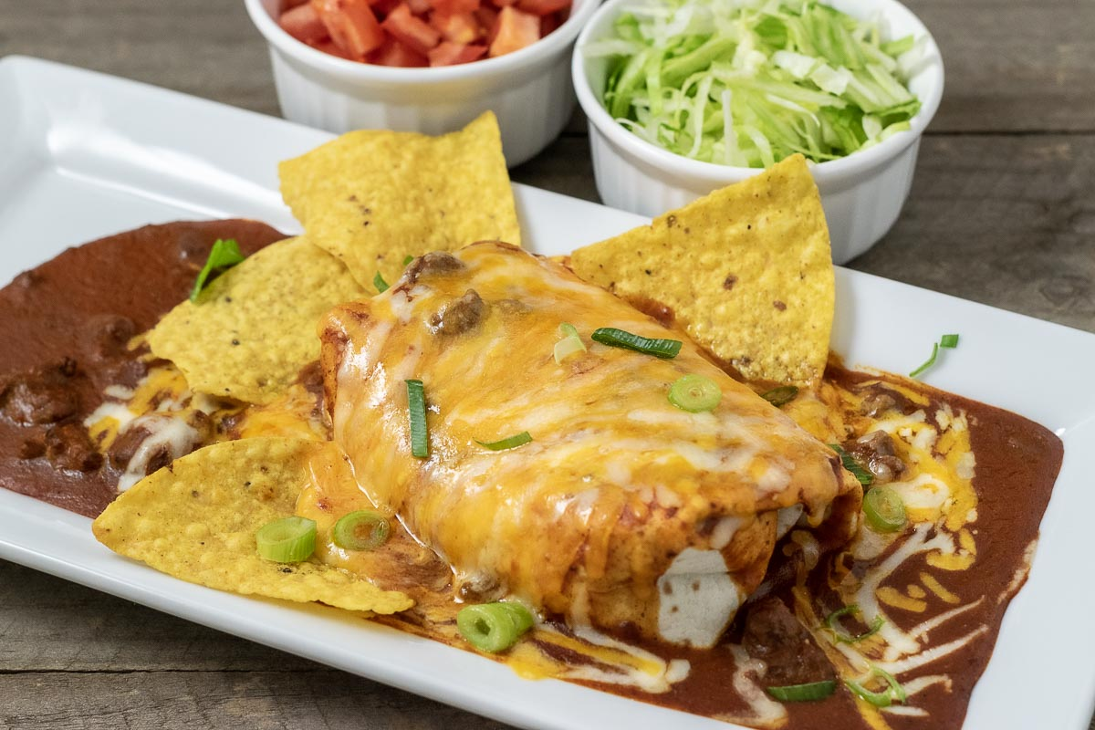 a large Beltline Bar copycat wet burrito on a platter with tortilla chips and sides of diced tomato and shredded lettuce