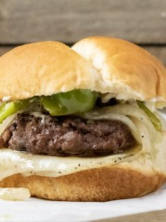 a close up front view of a philly cheesesteak burger