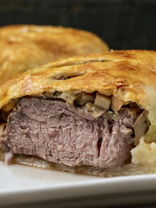 a front view of beef wellington that is cut open to see the filling