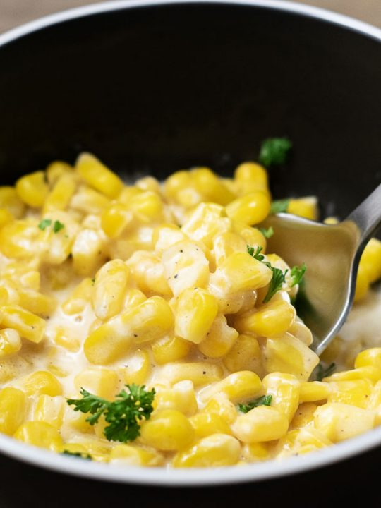 One Pot Cheesy Creamed Corn in a bowl with spoon lifting some corn
