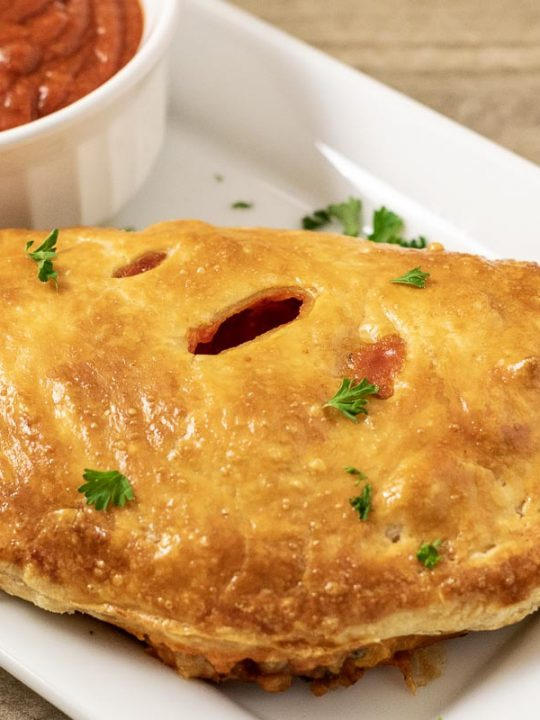 one Puff Pastry Pizza Calzone on a platter with a side of pizza sauce