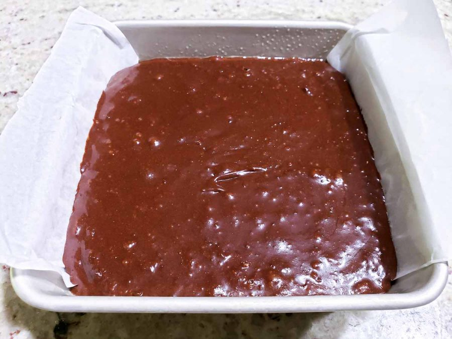 fudgy brownie batter in a cake pan