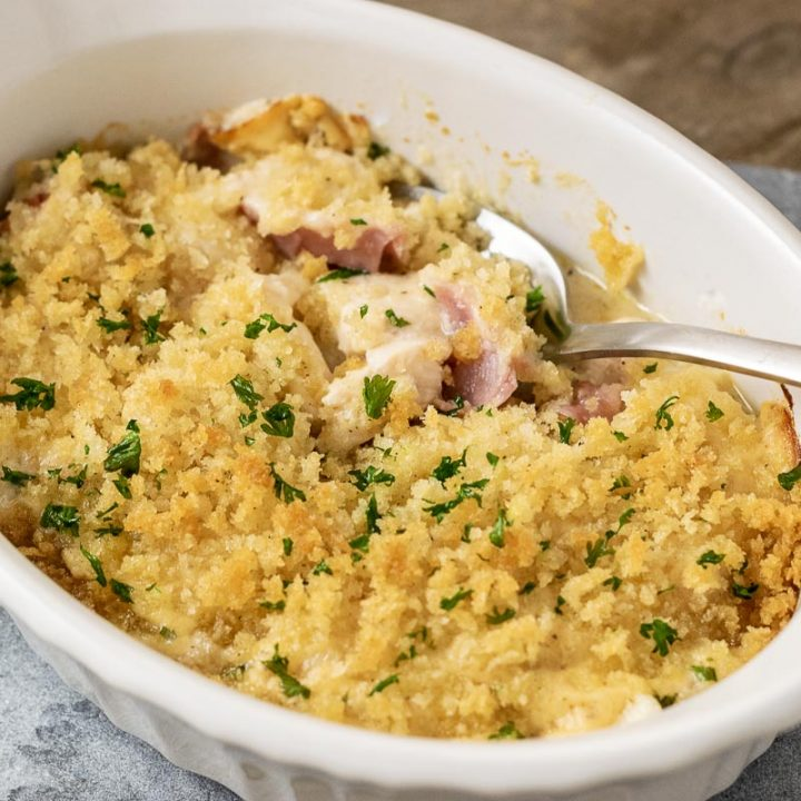 a close up front view of Low-carb Chicken Cordon Bleu Casserole with a spoon digging into the casserole
