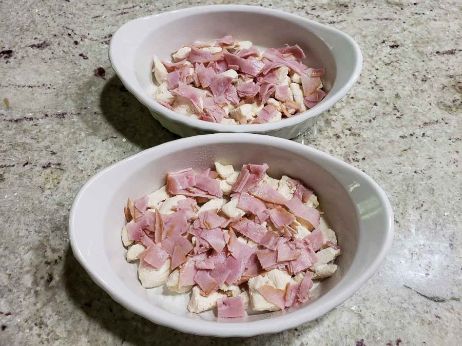 chopped ham lunchmeat layered over chicken in baking dishes