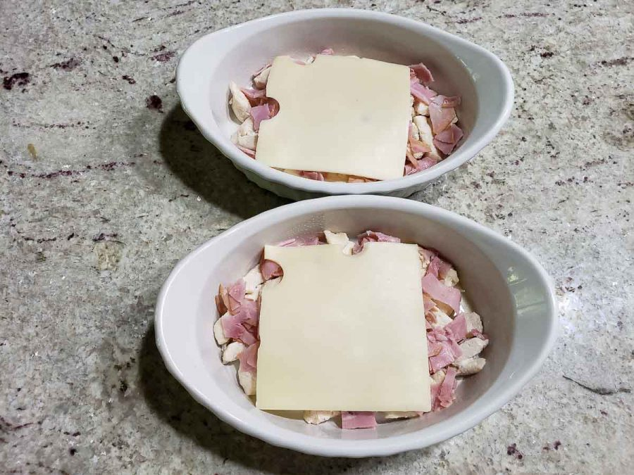 sliced swiss cheese layered over ham and chicken in baking dishes