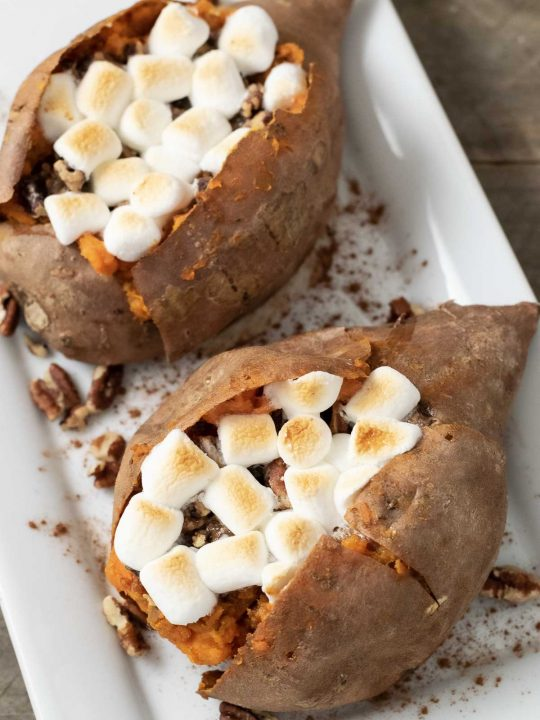 two sweet potatoes with marshmallow, brown sugar, butter, and pecan stuffing