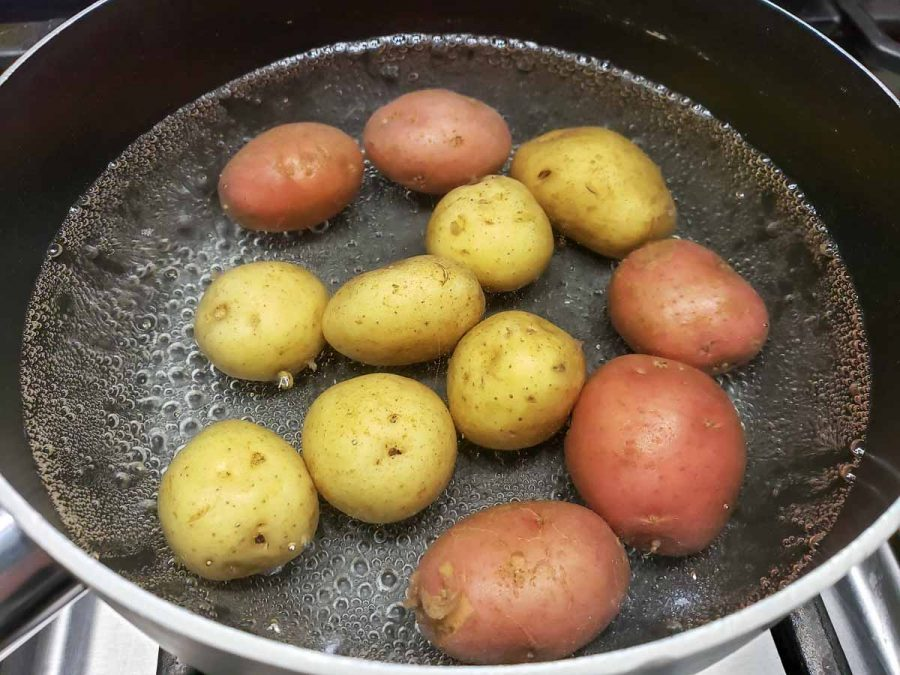 12 baby potatoes cooking in a pan