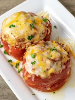 Two Slow Cooker Stuffed Peppers on a white platter