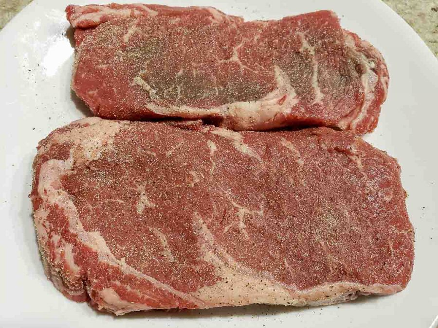 two ribeye steaks seasoned with salt and pepper on a plate