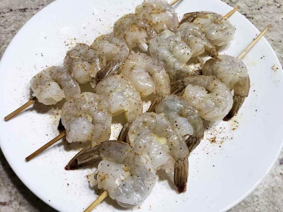raw shrimp on skewers on a plate seasoned with old bay seasoning