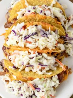 a plate filled with 5 Smoky BBQ Pulled Pork Tacos with Slaw