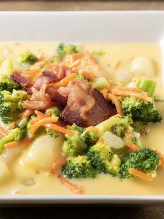 a bowl of cheesy potato soup with broccoli and bacon