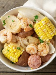 a bowl filled with shrimp, potatoes, onions, smoked sausage, and corn and sprinkled with old bay seasoning