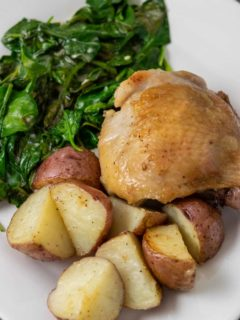 a plate with a golden brown chicken thigh with sides of red potatoes and spinach coated in sauce