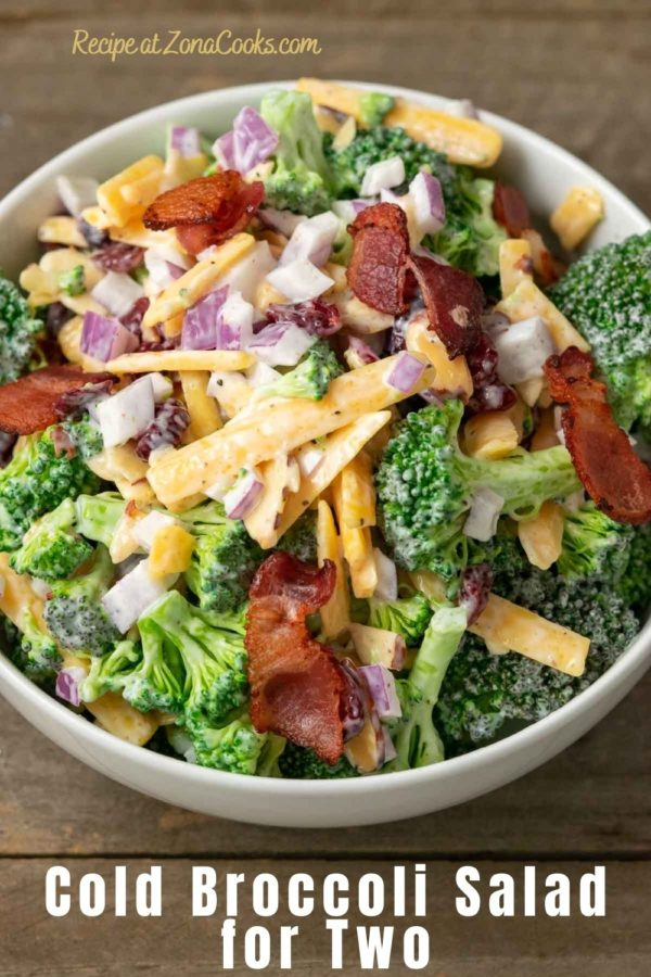a bowl filled with broccoli, red onion, bacon, cranberries and shredded cheese coated in a white creamy sauce and text reading recipe at zonacooks.com cold broccoli salad for two