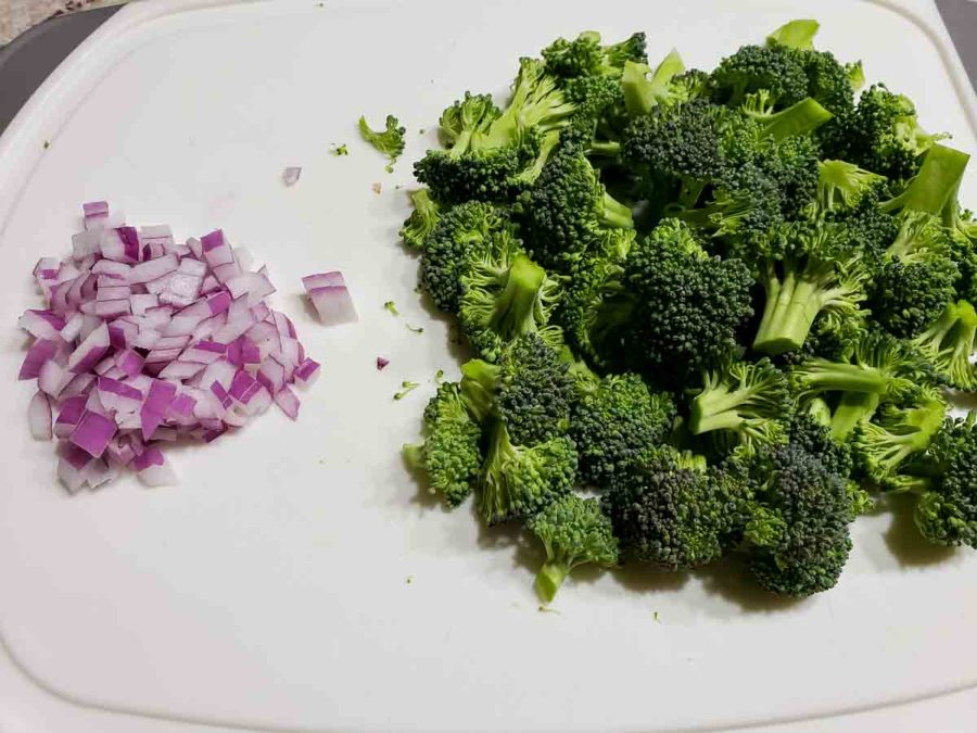 broccoli florets and diced red onions on a cutting board