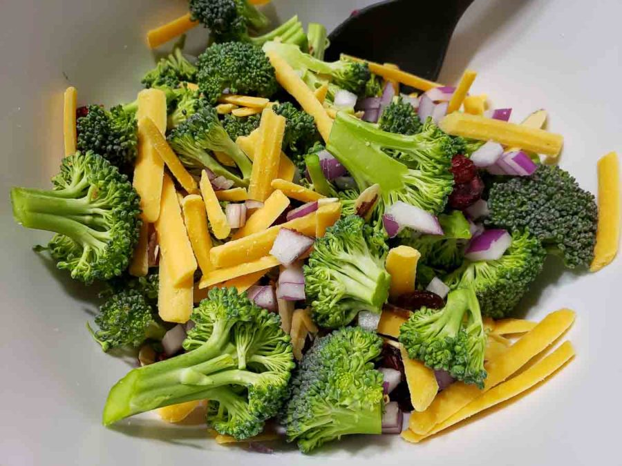 broccoli florets, diced red onion, dried cranberries, and shredded cheddar cheese in a bowl