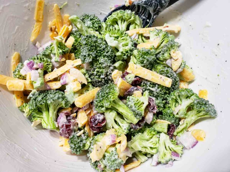 broccoli florets, diced red onion, dried cranberries, and shredded cheddar cheese coated in white creamy mayo in a bowl with a black spoon