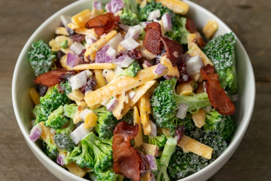 a close up front view of cold broccoli salad with a bowl filled with broccoli, red onion, bacon, cranberries and shredded cheese coated in a white creamy sauce