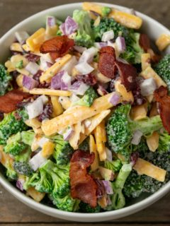 a white bowl filled with broccoli, red onion, bacon, cranberries and shredded cheese coated in a white creamy sauce