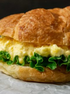 a close up front view of a large croissant filled with lettuce and creamy yellow chopped egg salad mixture