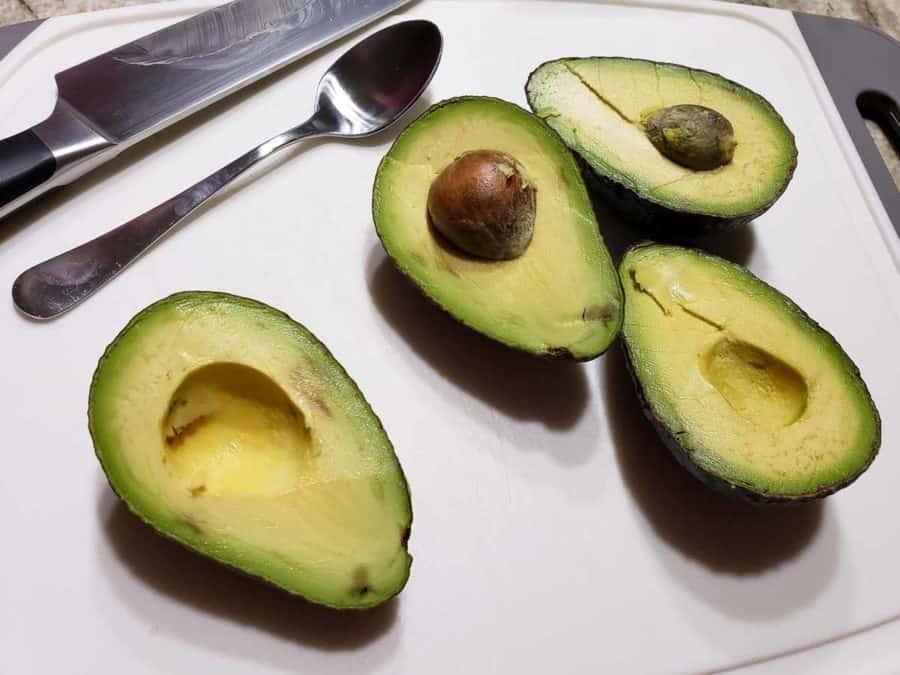 4 avocado halves on a cutting board