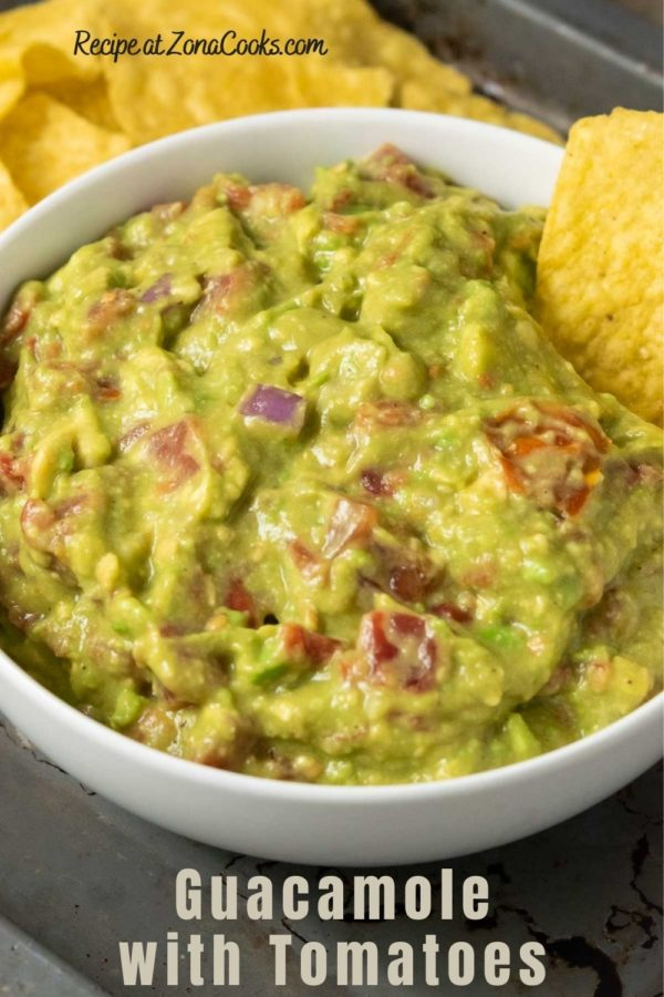a bowl of mashed green avocado and tomato mixture and a side of tortilla chips with one chip in the dip and text reading guacamole with tomatoes