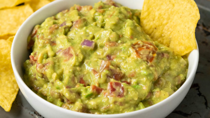 a bowl of mashed green avocado and tomato mixture with a tortilla chip dipped in and a side of more tortilla chips