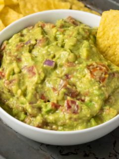 a bowl of mashed green avocado and tomato mixture and a side of tortilla chips and a single chip dipped in the guac