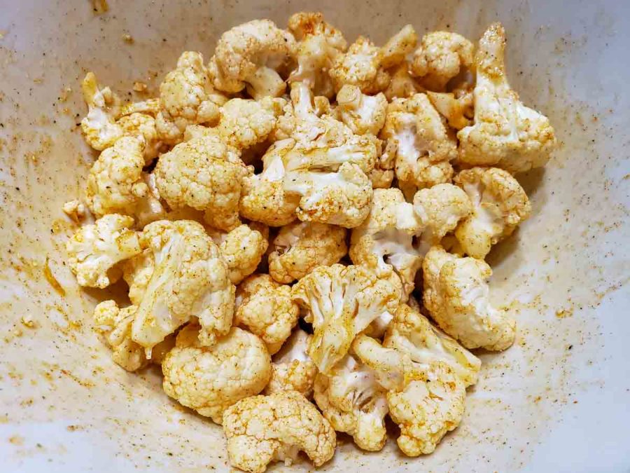 a bowl filled with cauliflower florets coated in oil and seasonings