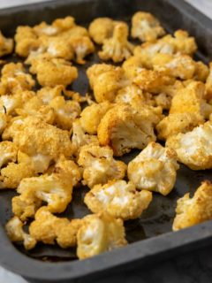 a small baking sheet pan filled with golden brown oven baked cauliflower florets