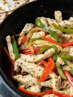 fire roasted tortillas and a cast iron skillet filled with sliced green pepper, red pepper, onions, and chicken in homemade fajita seasoning