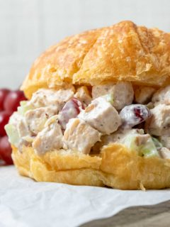 Chicken Salad Croissant with boneless chicken, grapes, almonds, and celery coated in a mayo dressing piled in a large buttery croissant roll.