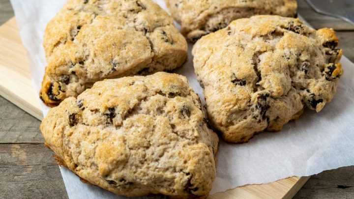 fluffy golden brown scones filled with cinnamon and raisins and topped with coarse sugar and sitting on parchment paper