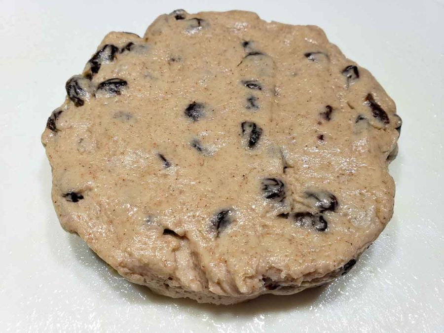 raisin scone dough formed into a 1 inch thick circle