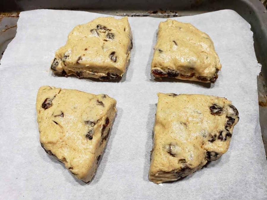 4 unbaked cinnamon raisin scones on a baking sheet
