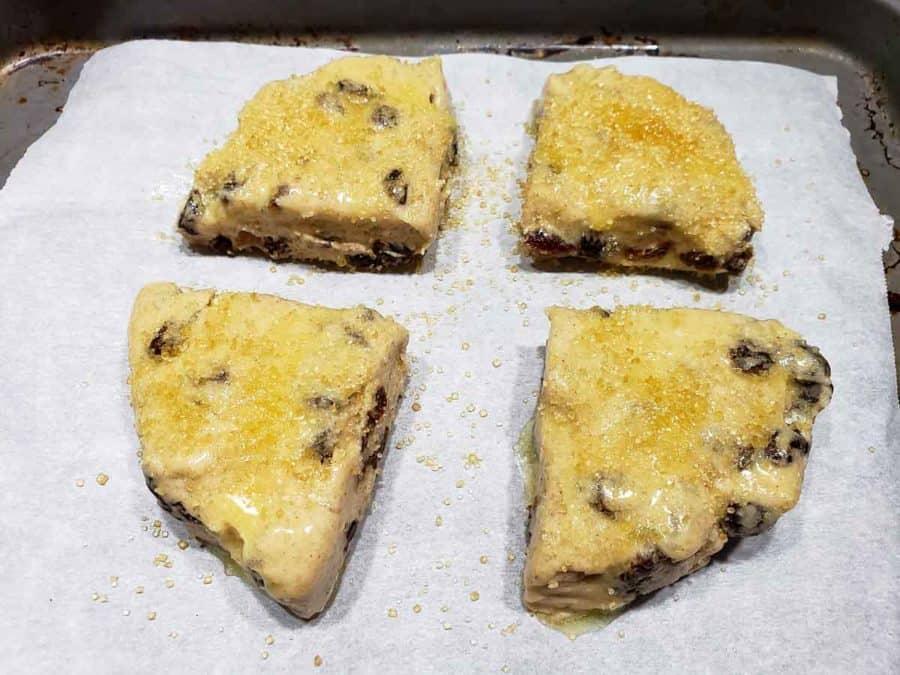 turbinado sugar sprinkled over butter on cinnamon raisin scone dough triangles