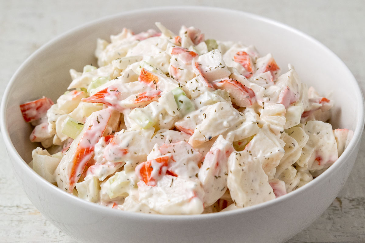 a bowl of cold seafood salad with chopped imitation crab meat combined with onion and celery in a creamy mayonnaise dressing.