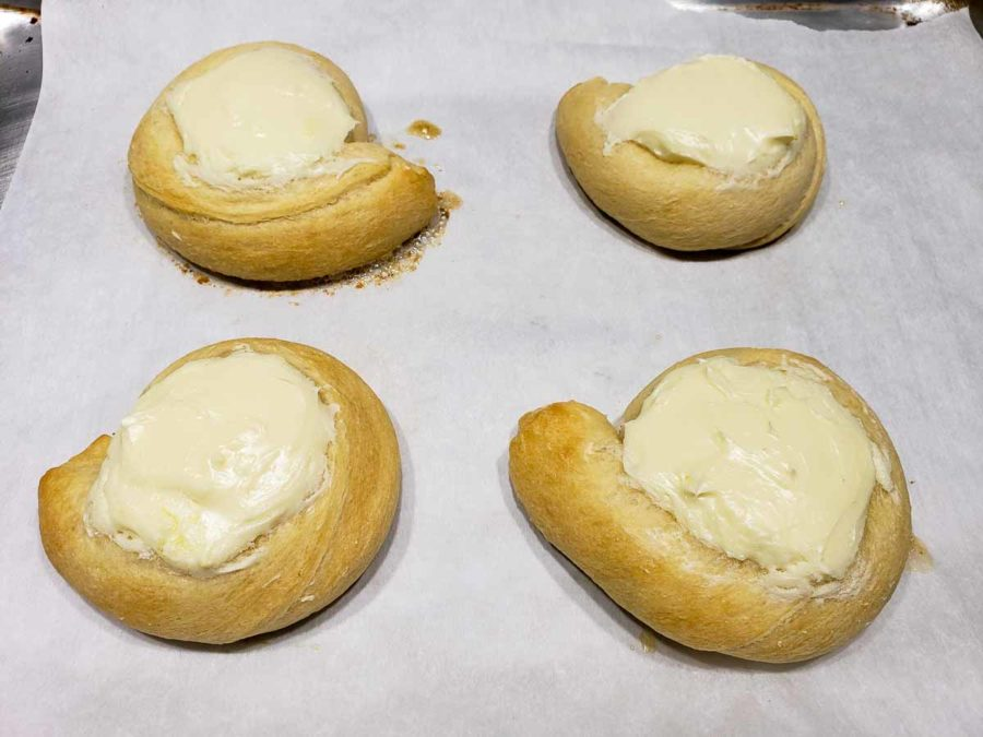 four baked cream cheese danishes on a baking sheet