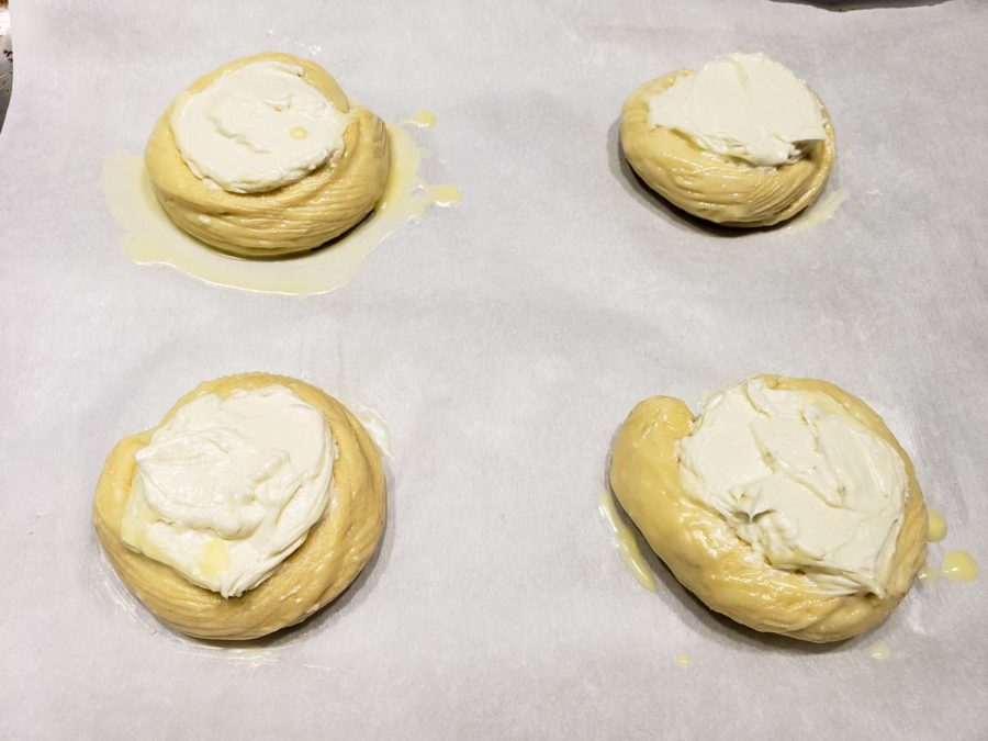 four crescent dough circles brushed with melted butter and filled with cream cheese filling