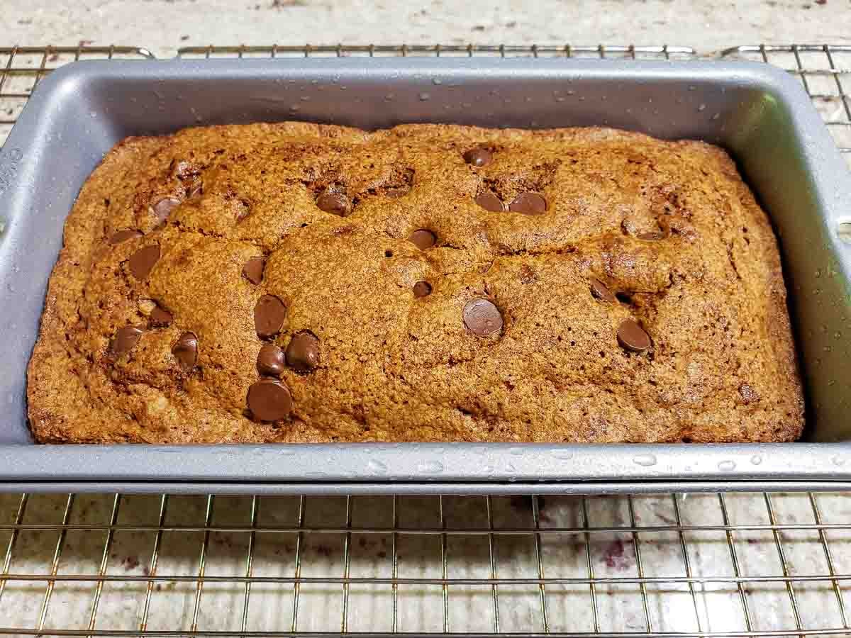 chocolate chip zucchini bread cooling in a pan on a wire rack.