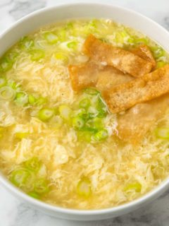 a bowl of egg drop soup topped with crispy wonton croutons.