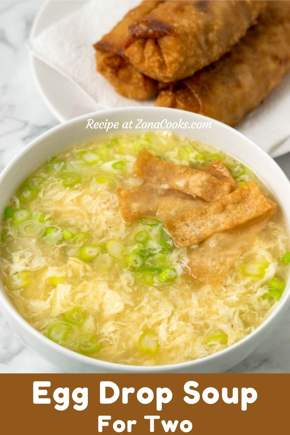 a bowl of egg drop soup and crispy wonton croutons with a side of eggrolls and text reading recipe at zonacooks.com egg drop soup for two.